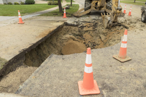 A large hole in a residential street, near a house driveway, the result of a broken water main. A backhoe is being used to remove damaged asphalt.